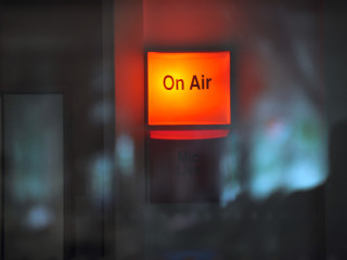 An illuminated 'On Air' sign outside a Radio/TV studio during a broadcast. Studio glass reflections